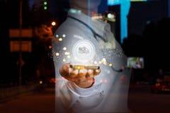 Een arts houdt een mobiele telefoon met het ziekenwagenteken die hierboven bij de achtergrond van de nachtstad hangen Het concept stock afbeeldingen