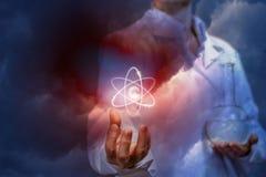 Een arts met een laboratoriumfles houdt een atoom royalty-vrije stock foto