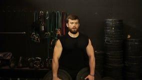 Een atleet heft een schijf, een oefening voor handen op stock videobeelden