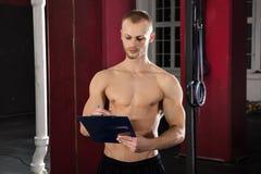 Een Atleet Man With Clipboard in de Gymnastiek stock foto