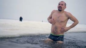 Een atleet probeert gebruikelijk te worden aan het bevriezen van water stock footage
