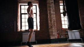 Een atletenmens die over het springtouw in de donkere gymnastiek springen stock videobeelden