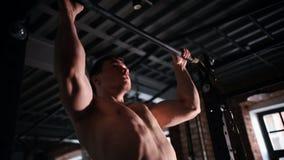 Een atletenmens die trekkracht UPS in de gymnastiek uitvoeren stock footage