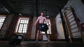 Een atletische mens die een groot gewicht vergen en het laten vallen op de vloer stock video