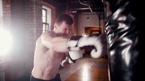 Een atletische mensenbokser die met een ponsenzak opleiden stock video