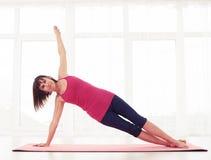 Een atletische zijplank van de donkerbruine praktijkenyoga stelt in de gymnastiek Stock Afbeelding