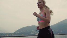 Een atmosfeer sport en fitness door de overzeese kust, mooi meisje, langzame motie stock footage