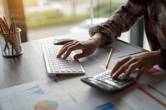 Een auditor die een calculator voor het berekenen met financieel verslag en het typen gebruiken op modern computertoetsenbord op  royalty-vrije stock afbeeldingen