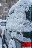 Een auto in de winter in het Parkeerterrein met sneeuw in een Blizzard wordt behandeld die Royalty-vrije Stock Afbeelding