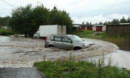 Een auto die door de overstroomde weg naast een ladingsvrachtwagen gaan met geblokkeerde motor in water Stock Foto's