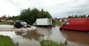 Een auto die via overstroomde weg naast 2 vrachtwagens met geblokkeerde motoren in water gaan Stock Fotografie