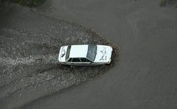 Een auto die zich door de overstroomde weg na intensieve douche bewegen Stock Afbeeldingen