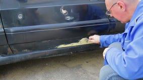 Een auto mechanische mens maakt roest-geplakte zetels op een autolichaam schoon stock footage