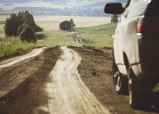 Een auto naast een windende landweg Stock Foto
