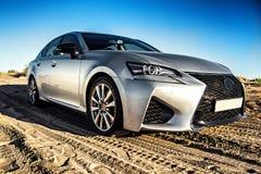 Een auto in zilveren kleur zonder emblemen in de woestijn in gouden uur royalty-vrije stock foto's
