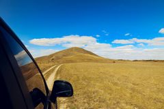 Een autoaandrijving aan de Heuvel onder de blauwe hemel Royalty-vrije Stock Fotografie