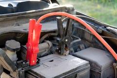 Een Autobatterij Jumper Cables met koperklemmen maakte aan de terminals vast royalty-vrije stock afbeeldingen