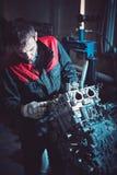 Een autowerktuigkundige in speciale kleren herstelt het verzetten zich interna royalty-vrije stock foto