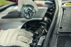 Een autowerktuigkundige vervangt een filter van de auto` s brandstof Royalty-vrije Stock Fotografie