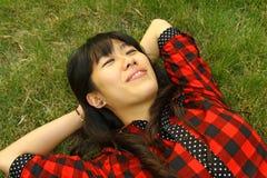 Een Aziaat die op het gras slaapt Stock Afbeeldingen