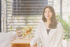 Een Aziatisch meisje in witte laag zitting en het glimlachen in de glasruimte van uitstekende koffie in Bangkok, Thailand 3,2017  Stock Foto