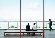 Een Aziatisch paar zit op houten bank kijkend over Yokohama-baai, Jap royalty-vrije stock foto