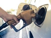 Een Aziatische hand vult de benzine Stock Foto