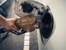 Een Aziatische hand vult de benzine aan een auto Stock Foto's