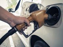 Een Aziatische hand vult de benzine aan een witte auto Stock Afbeelding