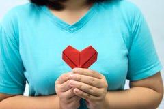 Een Aziatische hartorigami van de vrouwenholding voor haar borsta vrouw die rood hartdocument geven aan iemand De liefde en geeft stock afbeeldingen