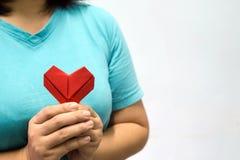 Een Aziatische hartorigami van de vrouwenholding voor haar borsta vrouw die rood hartdocument geven aan iemand De liefde en geeft stock fotografie