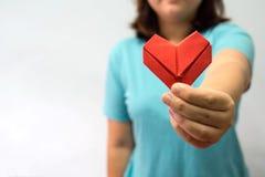 Een Aziatische hartorigami van de vrouwenholding voor haar borsta vrouw die rood hartdocument geven aan iemand De liefde en geeft royalty-vrije stock foto's
