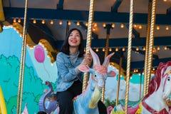 Een Aziatische jonge vrouw berijdt rotonde Royalty-vrije Stock Fotografie