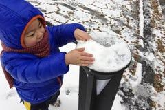 Een Aziatische jongen die met de sneeuw spelen stock foto's