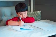 Een Aziatische jongen trekt een beeld Stock Afbeelding