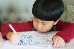 Een Aziatische jongen trekt een beeld Stock Fotografie