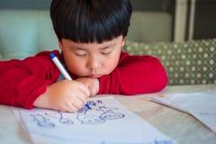 Een Aziatische jongen trekt een beeld Stock Foto's