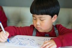 Een Aziatische jongen trekt een beeld Stock Afbeeldingen