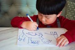 Een Aziatische jongen trekt een beeld Stock Foto