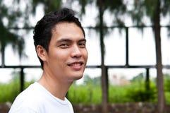 Een Aziatische mens die bij camara glimlachen Stock Foto