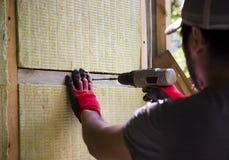 Een Aziatische mens die zijn huis verwarmen die steenwol gebruiken Royalty-vrije Stock Foto's
