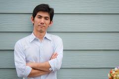 Een Aziatische mens kruist zijn wapen Stock Foto