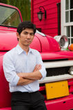 Een Aziatische mens kruist zijn wapen en helling tegen vrachtwagen stock afbeeldingen