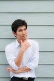 Een Aziatische mens kruist zijn wapen zoals denkend Stock Foto