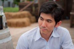 Een Aziatische mens met wit overhemd kijkt iets stock afbeelding
