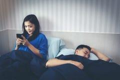Een Aziatische vrouw babbelt op een smartphone met haar vriend, w royalty-vrije stock fotografie