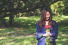 Een Aziatische vrouw die rood rozenboeket met groene aard houden Royalty-vrije Stock Foto