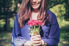 Een Aziatische vrouw die rood rozenboeket met groene aard houden Stock Afbeeldingen