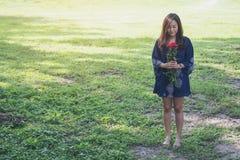 Een Aziatische vrouw die rood rozenboeket op grasgebied houden Royalty-vrije Stock Foto