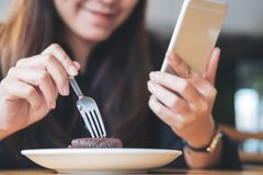Een Aziatische vrouw met smileygezicht die en slimme telefoon houden met behulp van terwijl het eten van brownie op houten lijst stock foto's
